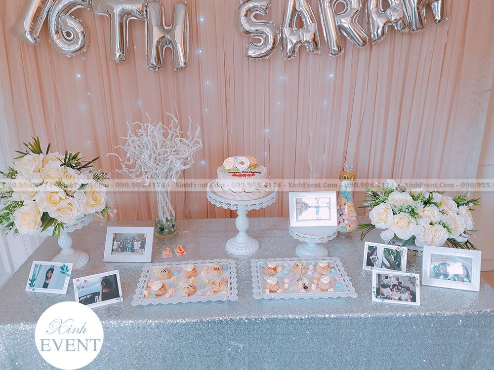 Bàn gallery sinh nhật bao gồm hoa, khăn trải bàn voan trắng, khung hình, bình marshmallow, bánh cupcakes