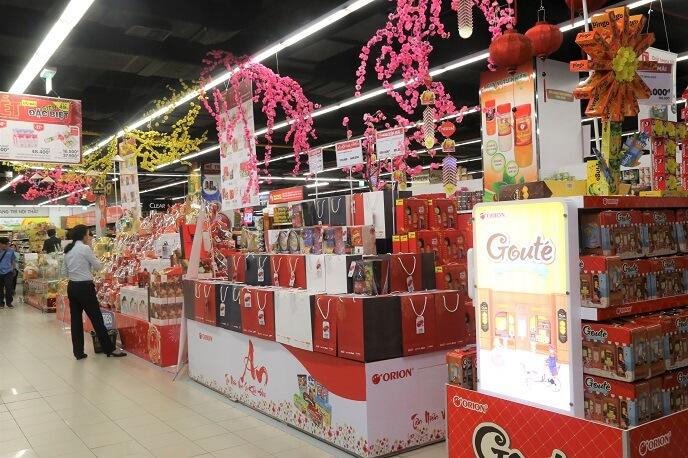 Đường dẫn siêu thị được trang trí nổi bật với hoa mai - đào cùng các món hàng mang màu sắc tết